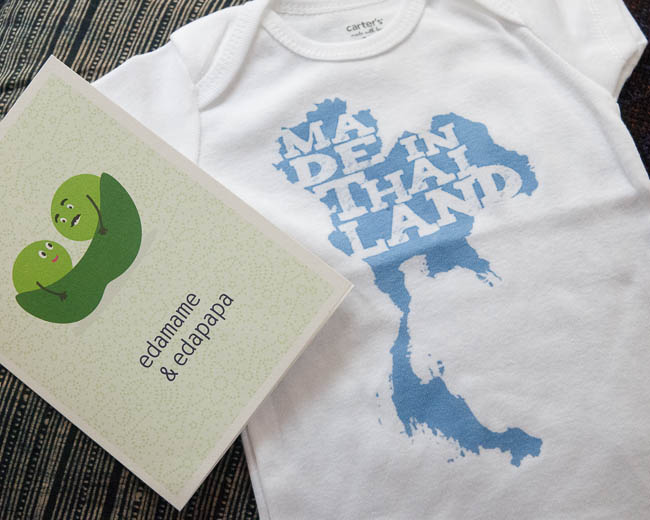 "A baby onesie that says ""Made in Thailand"" and an Edamame & Edapapa card"